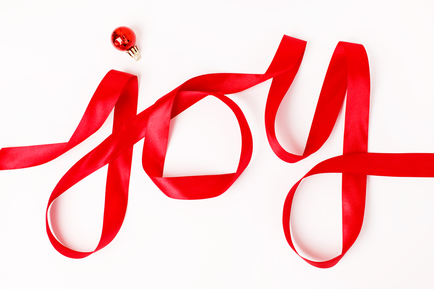 Joy word written in red ribbon on white background